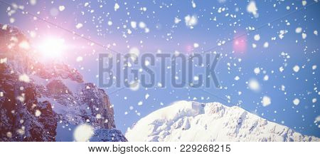 Snow falling against mountain top covered with snow