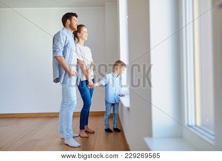 family, people and real estate concept - happy mother, father and little son looking through window at new home or apartment