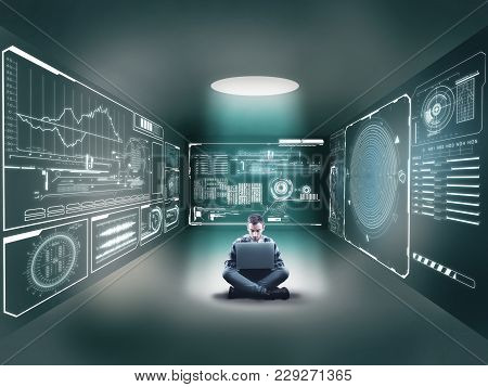Businessman Using His Laptop In Middle Of A Room And Studying Technical Graphics