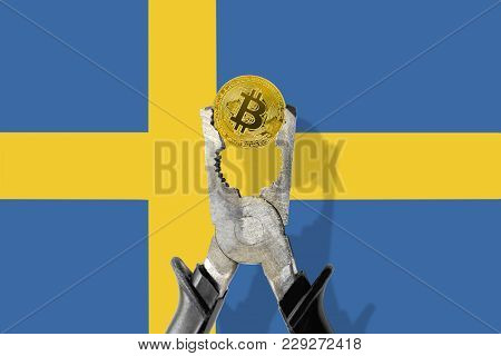 Bitcoin Coin Being Squeezed In Vice On The Sweden Flag Background; Concept Of Cryptocurrency Bitcoin