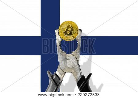 Bitcoin Coin Being Squeezed In Vice On The Finland Flag Background; Concept Of Cryptocurrency Bitcoi