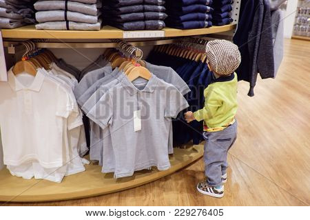 Cute Little Asian 18 Months / 1 Year Old Toddler Baby Boy Child Choosing & Buying Kids Clothes In Ga