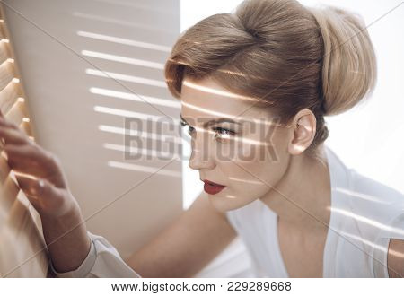 Woman With Concentrated Face With Makeup Looks Through Jalousie, Spying.