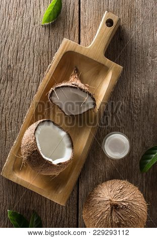 Creative Composition Coconut Half And Whole With Coconut Oil, Leaf And Coconut Products On Wooden Ta