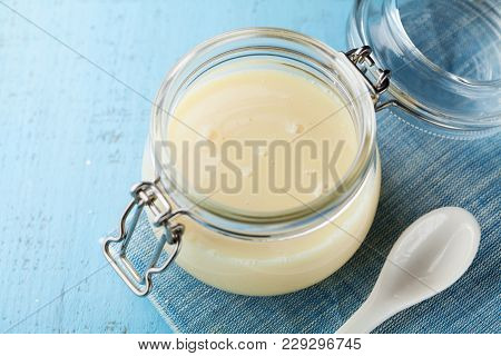Glass Jar With Condensed Milk Or Evaporated Milk On Blue Rustic Table.