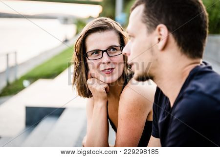 Young Woman In Focus Looking At Her Boyfriend