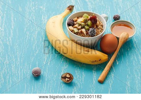 Oat Flakes Plate With Honey, Banana, Egg, Walnut On A Turquoise Wooden Table. 45 Degrees View Of Hea