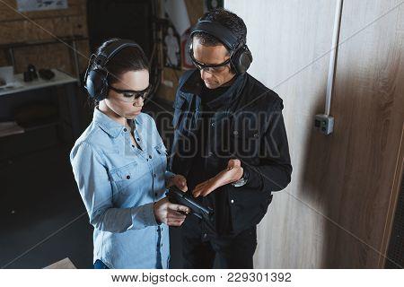 Male Instructor Describing Gun To Female Customer In Shooting Range