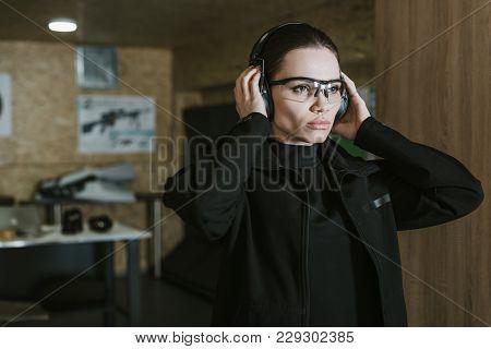 Attractive Girl Wearing Hearing Protectors In Shooting Range