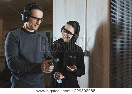 Smiling Shooting Instructor Talking To Client In Shooting Range