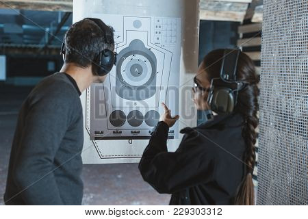 Shooting Instructor Pointing On Used Target In Shooting Range