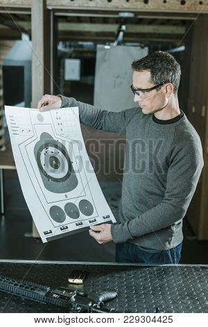 Shooter Looking At Used Target After Shooting In Gallery