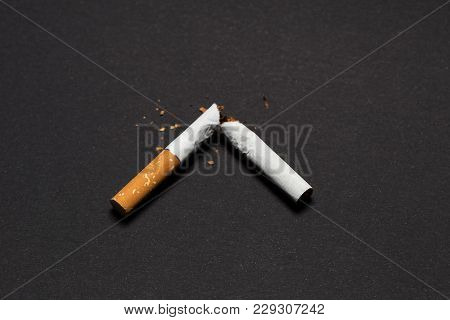 Harmfulness Of Smoking. Broken Cigarette On Black Background Harmfulness Of Smoking.