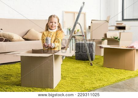 Adorable Child Holding Candle And Smiling At Camera During Relocation