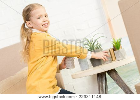 Cute Little Child Smiling At Camera While Putting Candles On Table During Relocation
