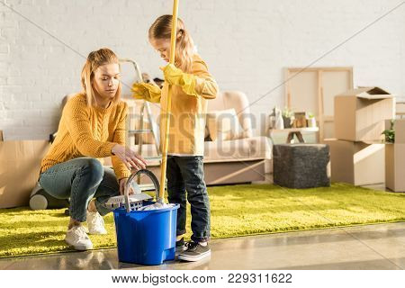 Mother And Daughter Cleaning Apartment With Mop After Relocation