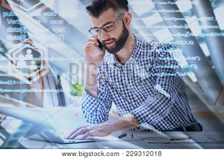 Handsome European Businessman Using Laptop And Talking On The Phone At Abstract Workplace With Html