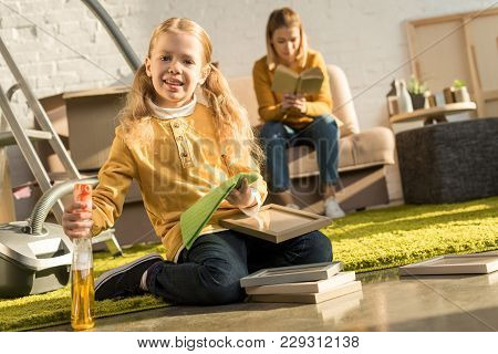 Cute Little Child Cleaning Frames And Smiling At Camera While Mother Reading Book After Relocation