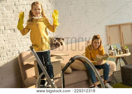 Child In Rubber Gloves Smiling At Camera While Mother Reading Book On Sofa During Relocation