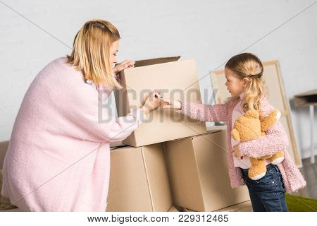 Mother And Daughter With Teddy Bear Signing Cardboard Boxes While Relocating