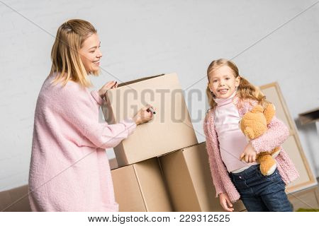 Happy Mother And Daughter With Teddy Bear Signing Cardboard Boxes While Relocating
