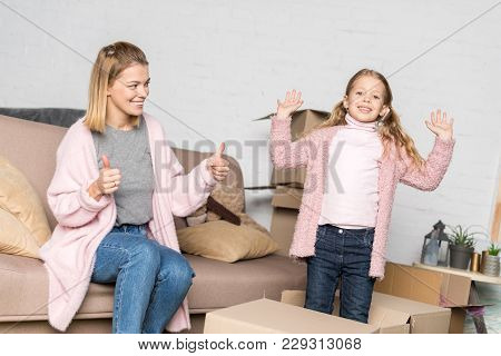 Happy Mother And Daughter Playing With Cardboard Boxes While Relocating