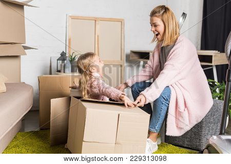 Happy Mother And Daughter Looking At Each Other While Playing With Cardboard Boxes During Relocation
