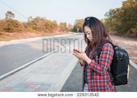 Woman Using Smartphone Find Directions By The Side Of The Road
