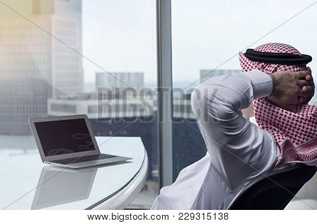 Saudi Arab Man Watching Laptop At Work Contemplating