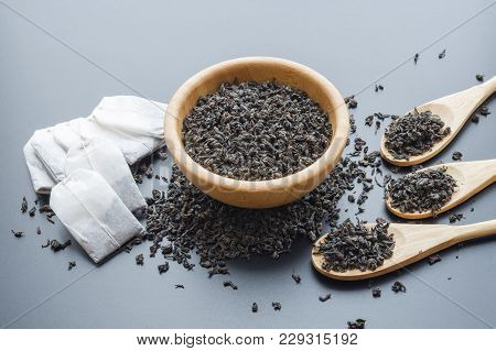 Single-time Tea Bags And Dry Black Tea Leaves In Wooden Bowl And Spoons, Scattered Over Dark Backgro