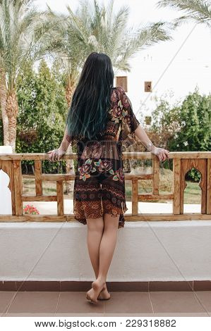 Back View Of Barefoot Girl Leaning At Railing And Looking At Beautiful Resort In Egypt