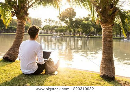 Digital Nomad Work In Park With Computer Online Over Wi-fi.