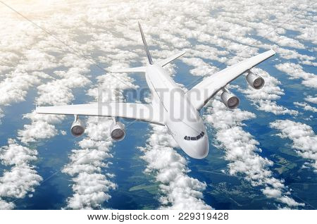 Passenger Huge Liner Plane Fly On A Fly Above Clouds And Blue Sky