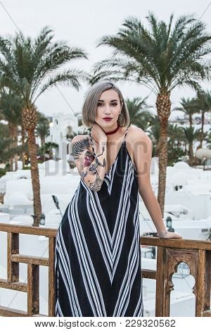 Beautiful Girl In Dress Looking At Camera While Leaning At Wooden Railing At Resort In Egypt