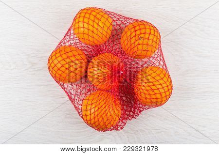 Ripe Oranges In Red Mesh On Wooden Table. Top View