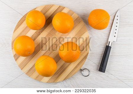 Ripe Oranges On Round Striped Cutting Board, Kitchen Knife On Wooden Table. Top View