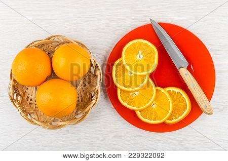 Whole Oranges In Wicker Basket, Slices Of Orange, Knife In Red Plate On Wooden Table. Top View