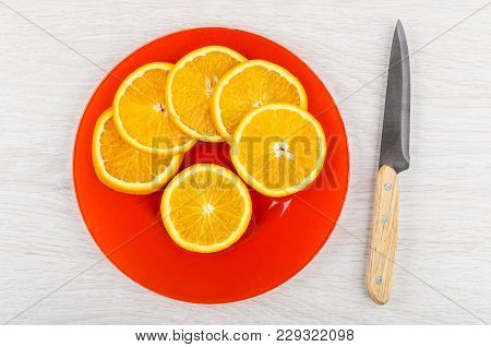 Slices Of Orange In Red Plate, Kitchen Knife On Wooden Table. Top View