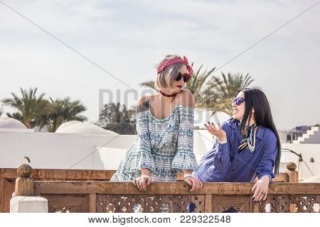 Beautiful Smiling Girls In Dresses And Sunglasses Talking While Leaning At Wooden Railing At Resort