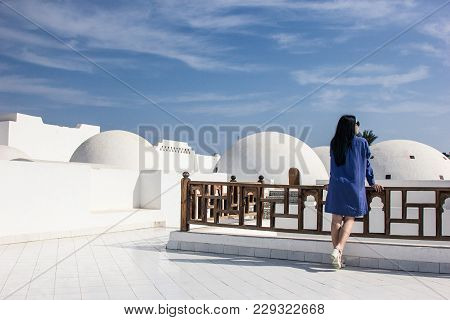 Back View Of Girl In Dress Leaning At Wooden Railing And Looking At Architecture In Egypt