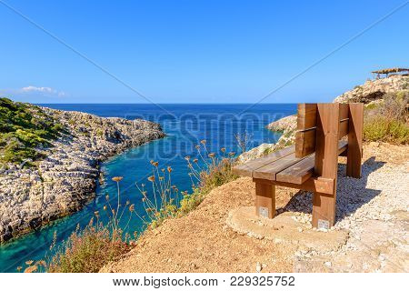 Bench On Cliff With View Of Bay With Crystal Sea Water. Korakonisi Island On Western Side Of Zakynth