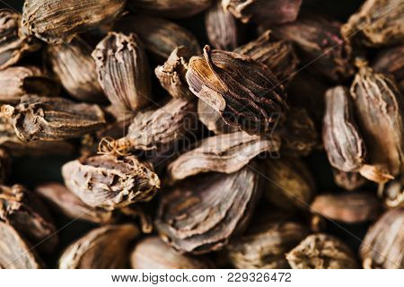 Black Cardamom Seeds In Wooden Bowl. Aromatic, Traditional Ingredient For Masala. Close-up For Asian