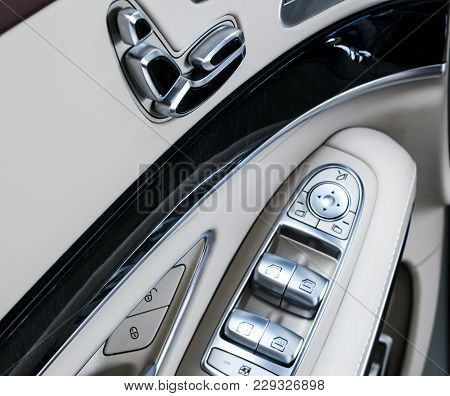 Door Handle With Power Seat Control Buttons Of A Luxury Passenger Car. White Leather Interior Of The