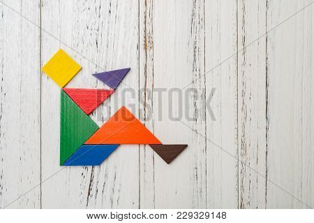 Wooden Tangram Shaped Like A People Sitting Down And Drinking Bowl Of Liquid