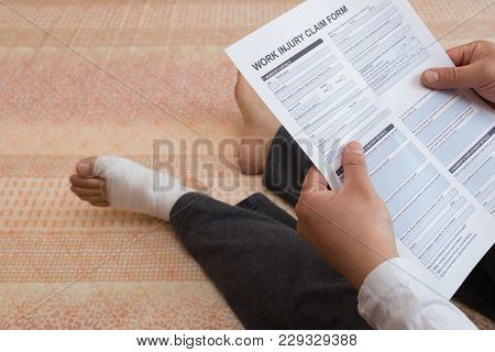 Man With A Wrapped Foot Sitting On Bed Reading The Work Injury Claim Form