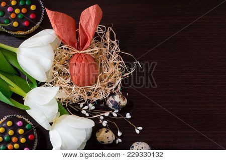 Brown Easter Egg In Form Of Rabbit In The Nest With Willow Branches, White Tulips, Cupcakes And Quai