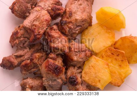 Mutton Shish Kebabs On Two Skewers With Baked Potato On The Plate