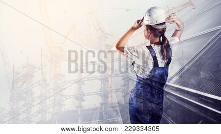 Portrait Of Builder In A Helmet On City Construction Background