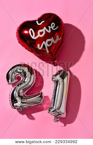 a heart-shaped balloon with the text I love you written in it and some silvery number-shaped balloons forming the number 21 against a pink background