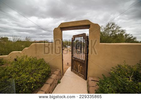 Storm Clouds Over Stucco Wall With Wood And Steel Door Or Gate. Scottsdale, Arizona, Usa.